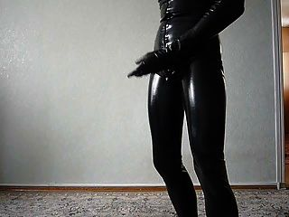 junger Mann in Latex-Catsuit wichst ab